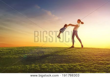 Happy loving family is having fun on nature in the summer. Young mother and her daughter are laughing and playing on meadow at sunset background.