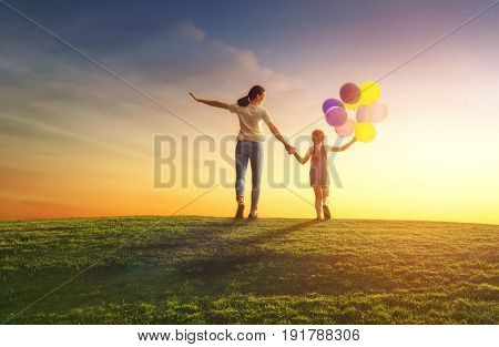 Happy loving family is having fun on nature in the summer. Young mother and her daughter are laughing and playing with balloons on meadow at sunset background.
