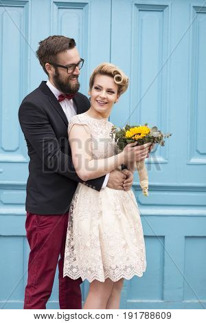 Newlywed couple standing next to a blue retro wooden door holding a sunflower wedding bouquet and hugging. Focus on the bride