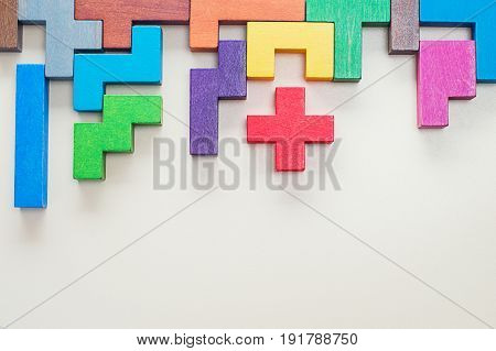 Different colorful shapes wooden blocks on beige background flat lay. Geometric shapes in different colors top view. Concept of creative logical thinking or problem solving. Copy space.