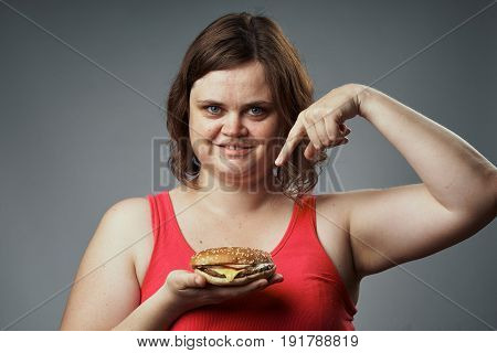 Tasty, woman shows a hamburger, a woman with a hamburger on a gray background, meal.