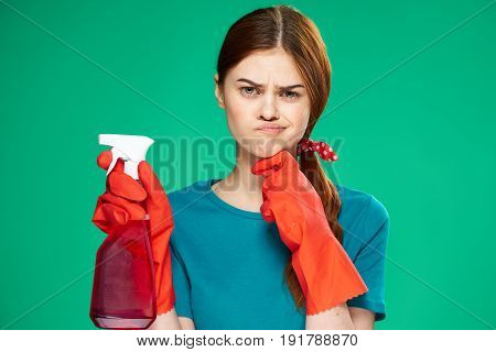 Cleaning, woman with a cleanser, woman in red gloves, on a green background.