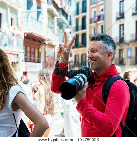 Photographer on San Fermin. Photojournalist. People celebrate San Fermin festival in traditional white and red clothing with red necktie, 06 July 2016, Pamplona, Navarra, Spain.