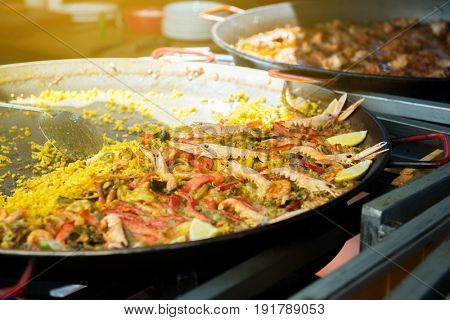 Street food in San Fermin feast, Pamlona, Navarra, Spain. Paella. Rise with seafood and vegetables. Spanish traditional cuisine. Spanish national dish, image toned and noise added.