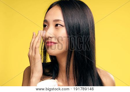 Woman applying cream on face woman on yellow background portrait.