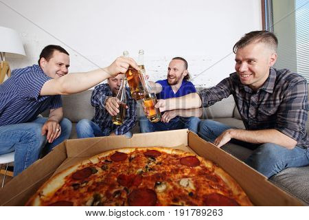Friends Clink Beer Over Pizza