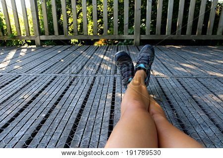 Girl takes a break from hiking on a wooden bridge