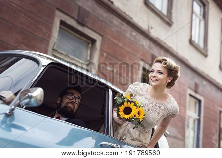 Young newlywed couple in a retro vintage car groom driving while bride is waving through a window while they are leaving on their honeymoon. Focus on the bride