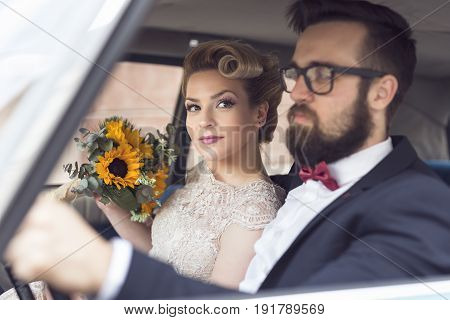 Young newlywed couple sitting in a retro vintage car going away on a honeymoon. Focus on the bride