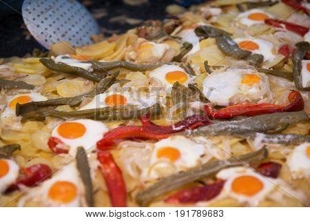 Street food in San Fermin feast, Pamlona, Navarra, Spain. Fried eggs. Scrambled eggs with vegetables. Spanish traditional cuisine. Spanish national dish.