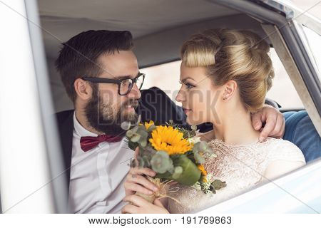Young newlywed couple sitting in a retro vintage car hugging and going away on a honeymoon. Focus on the bride