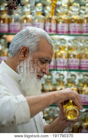MEDINA, SAUDI ARABIA, March 2015: The salesman in a traditional perfume store.