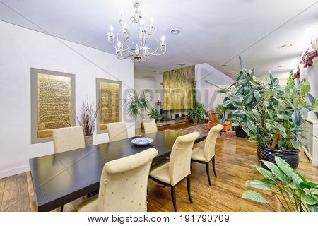 Large dining table in the interior of a modern living room with designer renovation.