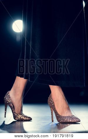 low section of stylish glamour woman walking in glitter high heels and long black dress