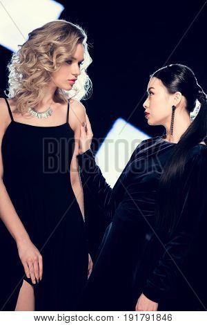 Two Sensual Glamour Multiethnic Women Spending Time In Black Evening Dresses At Event