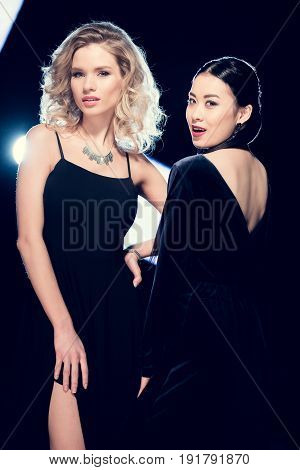 Two Seductive Glamour Multicultural Women Posing In Black Evening Gowns And Looking At Camera At Par