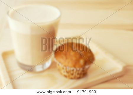 Glass cup of cappuccino with muffin on a wooden background; blurred background