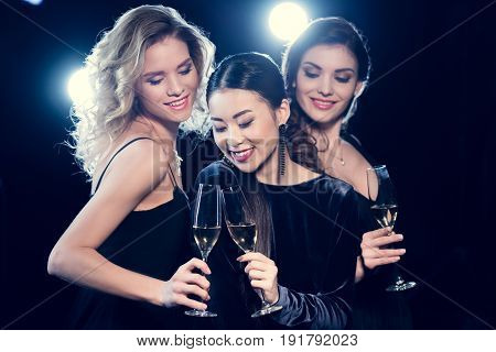 Beautiful Young Women In Stylish Dresses Partying And Drinking Champagne Together
