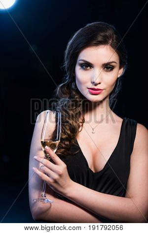 Portrait Of Seductive Young Woman In Evening Gown Holding Glass Of Champagne Looking At Camera