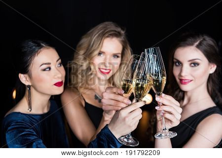 Young Women In Stylish Dresses Clinking Glasses With Champagne In Hands