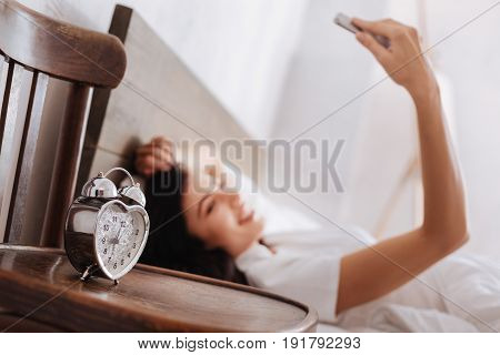 Five more minutes for a selfie. Selective focus on a silver alarm clock standing on a wooden chair with a woman taking a self portrait while lying in bed.