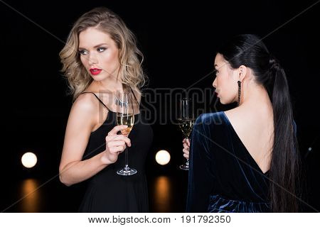 Beautiful Multicultural Women In Evening Gowns Holding Champagne Glasses At Party