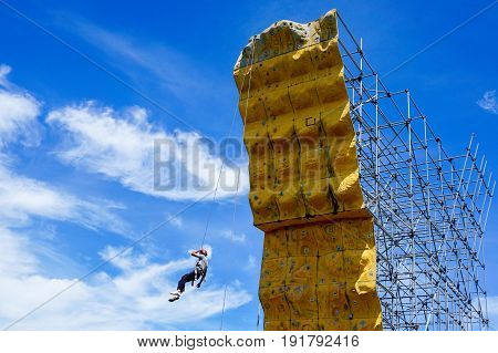 Labuan,Malaysia-May 21,2017:Man with safety equipment climb on yellow climbing wall in Labuan,Malaysia.It is an activity in which participants climb up,down or across artificial rock walls