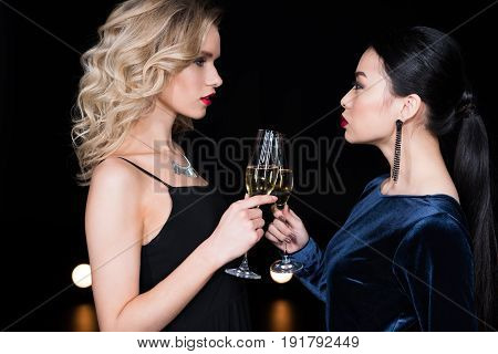 Young Glamour Women In Evening Gowns Clinking With Champagne Glasses At Party