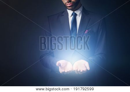 Light radiating from businessman hands. New idea, prime product concept.