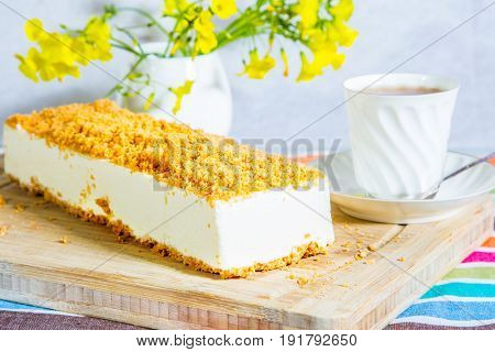 Professional bakery. Gorgeous white cheesecake, sprinkled with sweet crumbs. The background is  vase with daisies and porcelain cup with hot tea