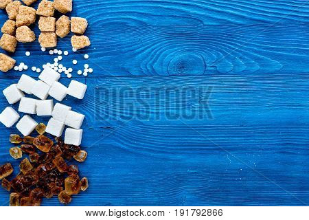 sugar in lumps for sweet food cooking on kitchen blue table background top view mock up