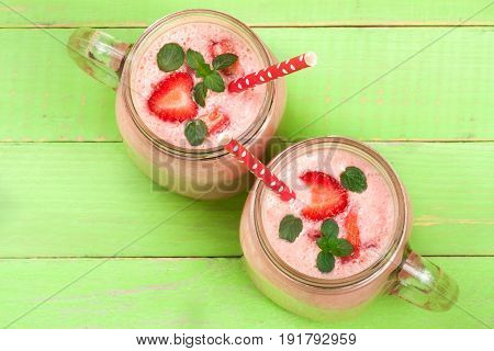 Glass of strawberry yogurt or smoothie with mint leaves on green wooden background. Top view.