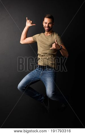 Happy handsome young man jumping and dancing. Black background