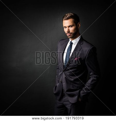 Handsome young businessman standing confident on black background. Smart boss, manager portrait with hands in pockets