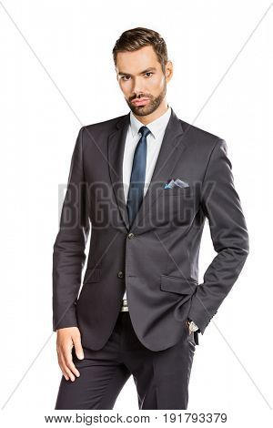 Handsome young businessman standing confident on white background. Smart boss, manager portrait with hand in pocket
