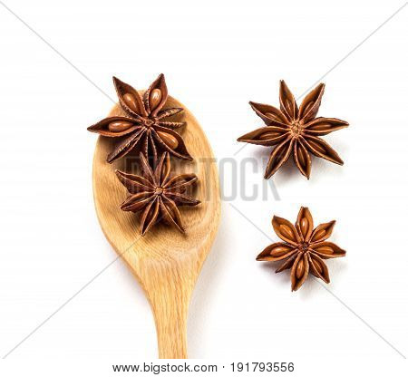 Close up brown star anise spice in wooden spoon isolated on white background