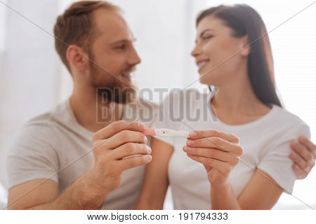 The happiest moment of our lives. We have Selective focus on a pregnancy test in hands of a newly married couple hugging and smiling at each other on the background.