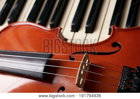 Classical musical stringed instrument violin on piano keys. Fiddle on piano keyboard.