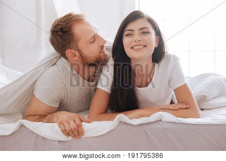 You are my everything. Young couple relaxing in bed and having a talk underneath a blanket at home.