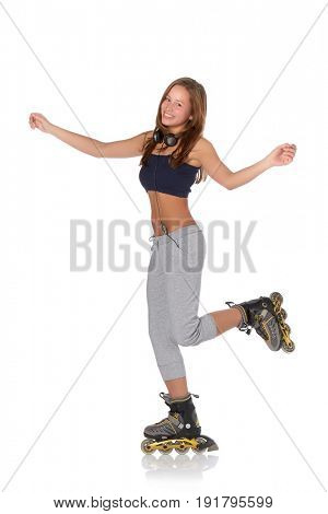 The beautiful girl with earphones in rollerskates on a white background.