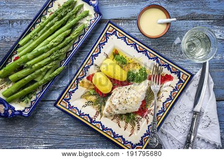 Codfish Fillet with green Asparagus and boiled Potatoes as top-view on a plate