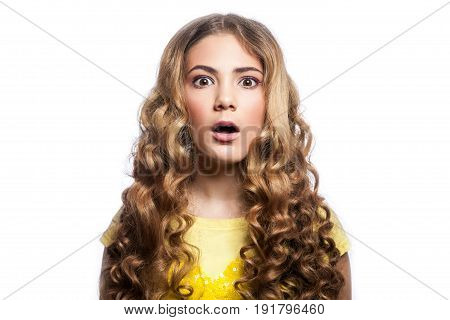 Portrait of surprised girl with wavy hairstyle and yellow t shirt. studio shot isolated on white background.