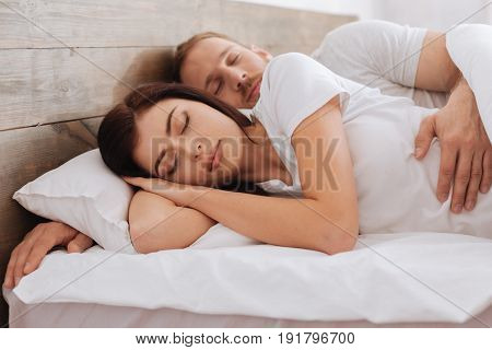 Sleeping tight. Loving couple hugging while having a rest and sleeping together in bed.