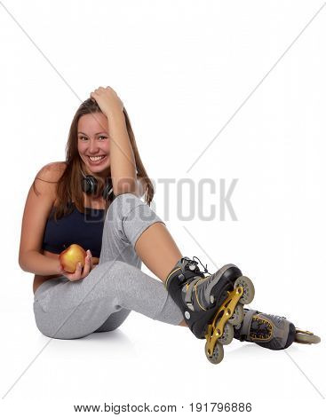 The beautiful girl  in rollerskates with an apple on a white background.