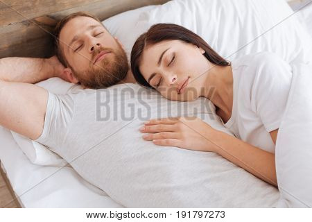 Sleeping beauty. Millennial lady sleeping tight on her husband chest during an afternoon nap at home.