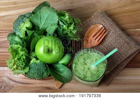 close up green apple with mixed green vegetable and green juice in a basket and wooden fork and spoon for healthy organic green food concept