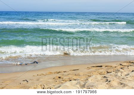 Seascape, sea with not big waves, of blue and green colour with part of sandy beach and sky. Recorded on Black sea, Bulgaria.
