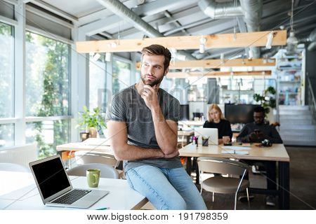Picture of concentrated thinking young man sitting on table in office. Looking aside.