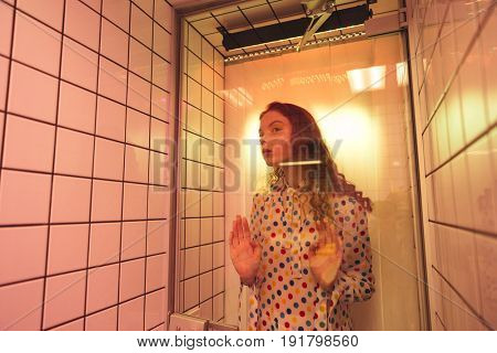 Fashion portrait of young redhead curly woman standing in cafe at latrine at shower. Looking aside.