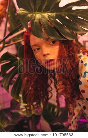 Fashion portrait of serious young redhead curly lady standing in cafe near latrine and plants. Looking aside.
